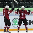 ZUG, SWITZERLAND - APRIL 16: Latvia's Kristaps Zile #7 celebrates with Karlis Cukste #6 after a first period goal against Canada during preliminary round action at the 2015 IIHF Ice Hockey U18 World Championship. (Photo by Francois Laplante/HHOF-IIHF Images)