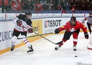 ZUG, SWITZERLAND - APRIL 18: Canada's Jansen Harkins #12 moves the puck up the ice while Switzerland's Calvin Thurkauf #18 defends during preliminary round action at the 2015 IIHF Ice Hockey U18 World Championship. (Photo by Francois Laplante/HHOF-IIHF Images)