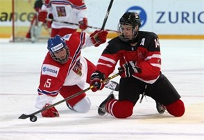 ZUG, SWITZERLAND - APRIL 19: Canada's Matt Barzal #14 plays the puck from his knees as the Czech Republic's Michael Spacek #15 looks on during preliminary round action at the 2015 IIHF Ice Hockey U18 World Championship. (Photo by Francois Laplante/HHOF-IIHF Images)